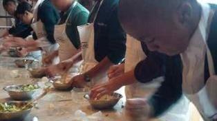 Mani di ragazzi impegnati a fare i tortellini