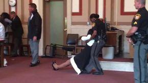 Giudice condannata sotto choc, trascinata in prigione a braccia