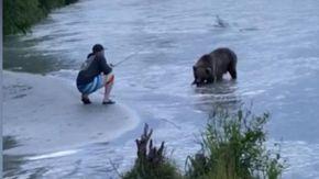 Sta pescando e arriva un orso: l'uomo resta immobile ma il finale è inatteso