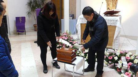 Un drappo sul tavolino e fiori bianchi: le esequie del 15enne cinese