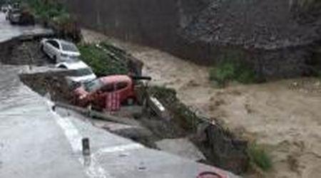 Inondazioni in Cina, la strada crolla e le macchine finiscono nel torrente di acqua e fango