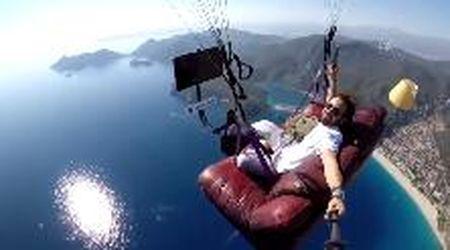 Si lancia col parapendio seduto sul divano: in volo guarda la tv e mangia patatine